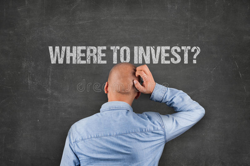 Confused Businessman Looking At Where To Invest Text On Blackboard stock photography