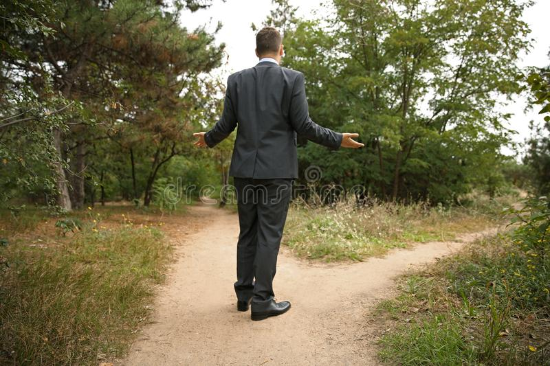 Confused businessman standing at crossroads. Concept of choice royalty free stock images