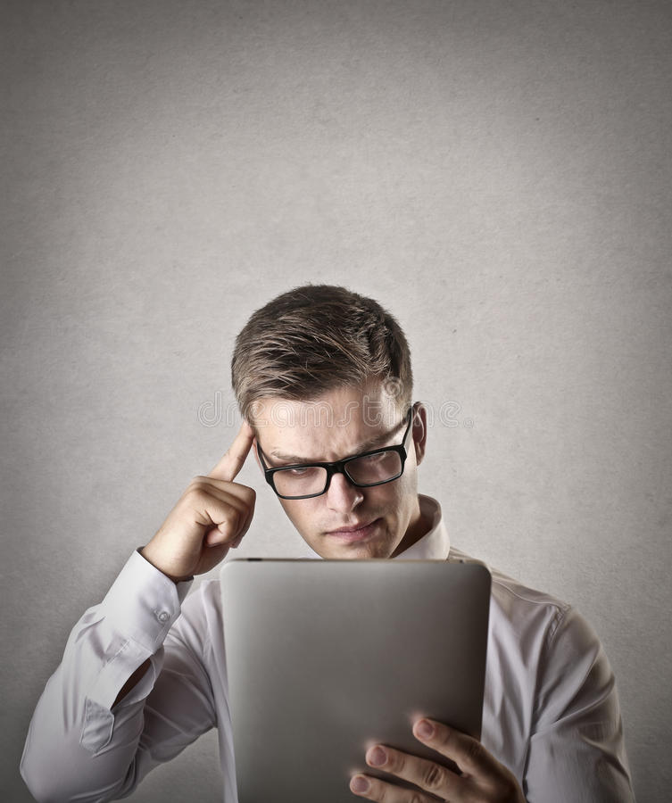 Confused businessman using a tablet stock image