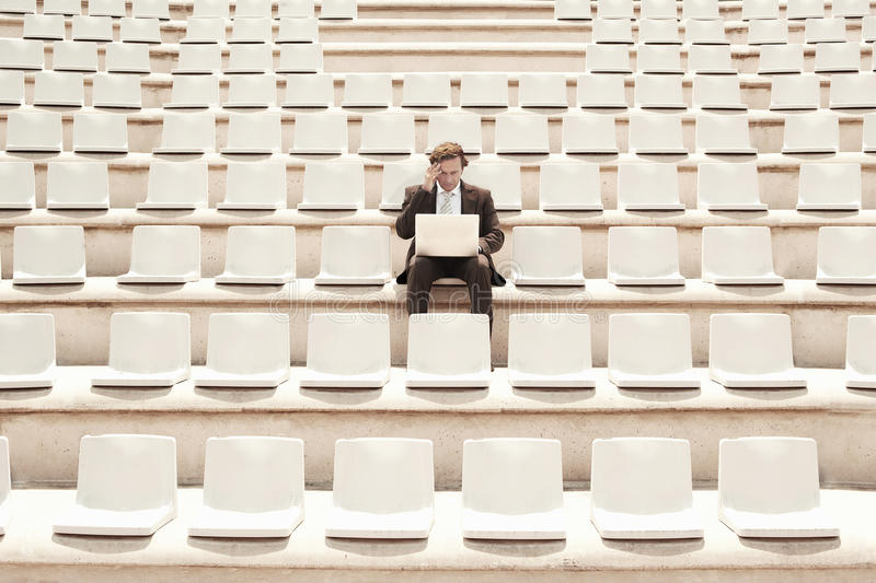Confused Businessman Working On Laptop In Center Of Empty Auditorium royalty free stock photography
