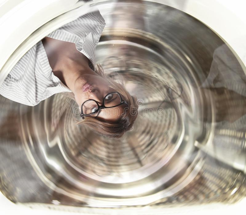 Confused businesswoman has dizziness inside a washing machine. Concept of stress and overwork stock images