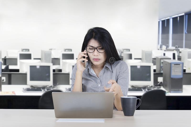 Confused businesswoman with damaged laptop royalty free stock photos