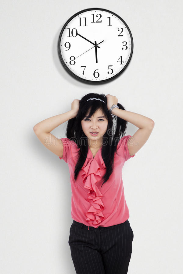 Confused businesswoman under a clock. Portrait of stressed employee grabbing her hair under a clock on the wall stock images