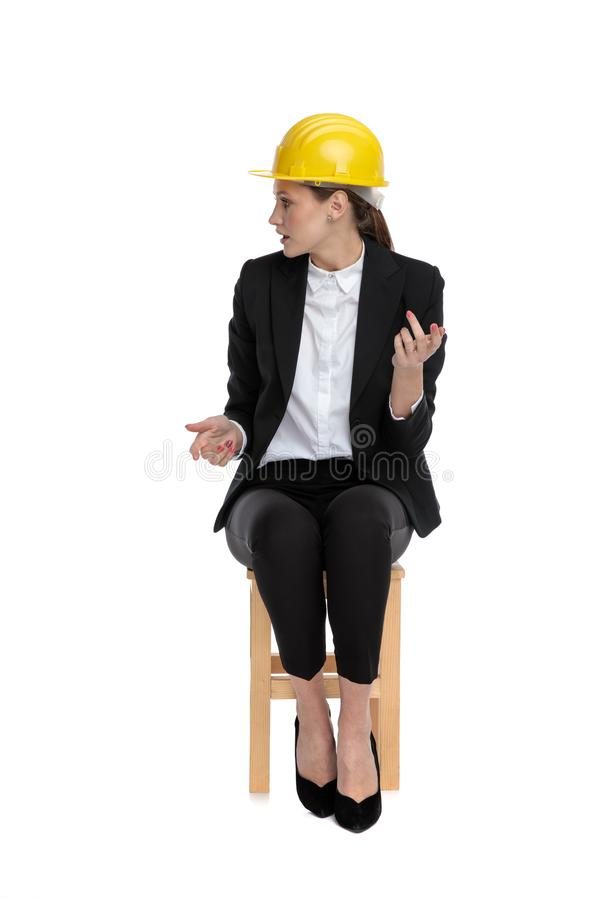 Businesswoman wearing yellow helmet looking aside confused royalty free stock photos
