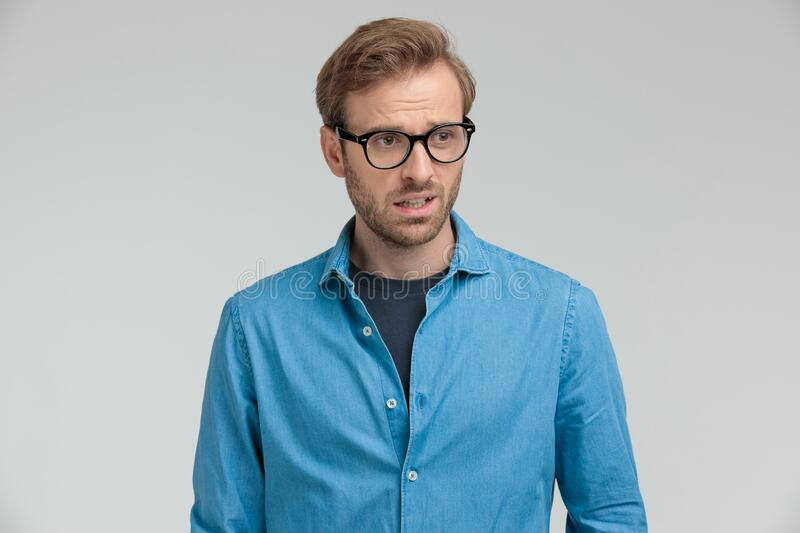Confused casual young man looking to side royalty free stock images