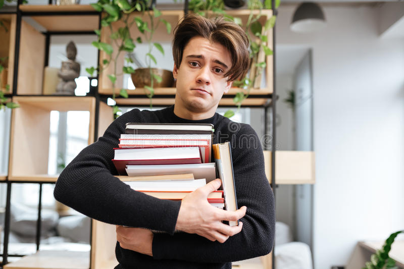 Confused caucasian student in library holding books royalty free stock photography
