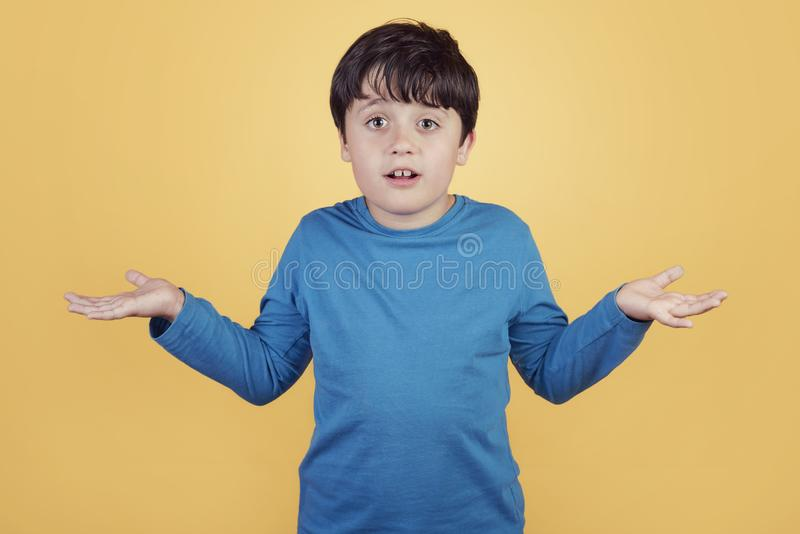 Confused child asking about. On yellow background royalty free stock images