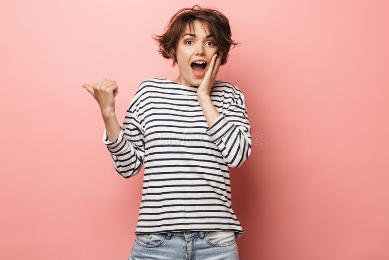Confused chockat härligt posera för kvinna som isoleras över rosa peka för väggbakgrund royaltyfri fotografi