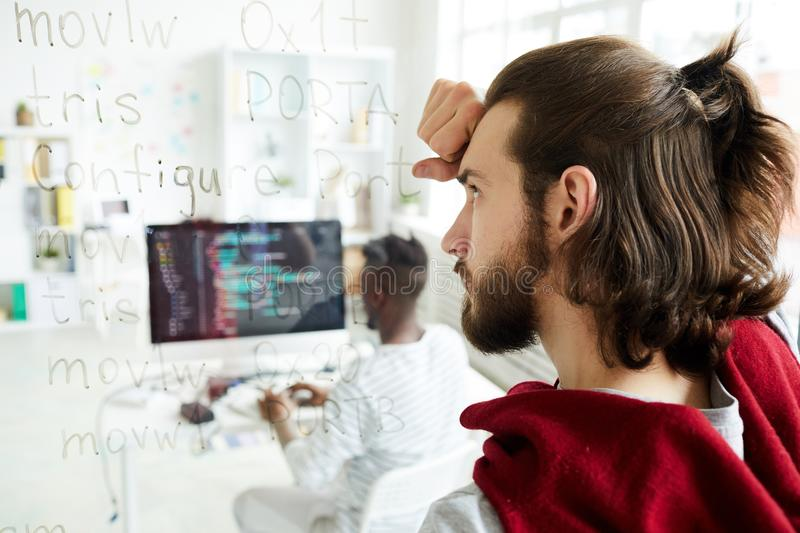 Confused coder looking at computer text. Serious confused hipster coder with pony tail looking at computer text while brainstorming about solution in modern royalty free stock photo