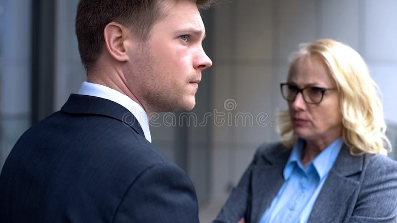 Confused company trainee standing front of angry female boss, work confrontation royalty free stock images