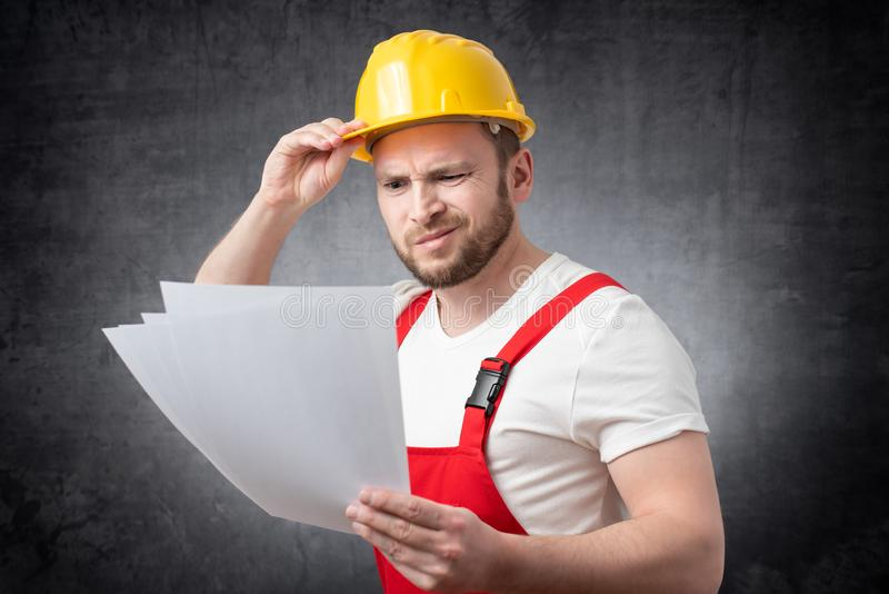 Confused construction worker holding papers stock images