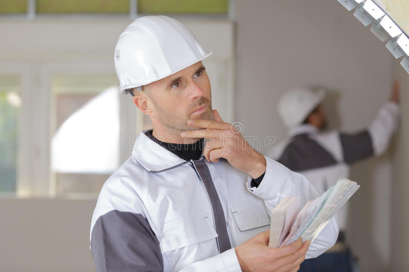 Confused construction worker holding spirit level in new house royalty free stock photos