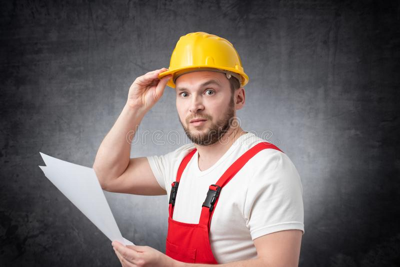 Confused construction worker holding papers royalty free stock photo