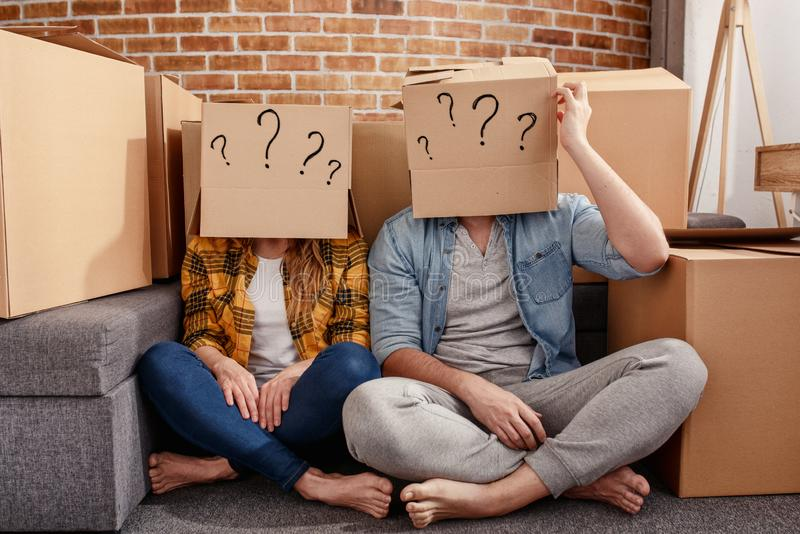 Confused couple of having to move and arrange all the packages. Concept of success, delusion, change , future, confusion stock images