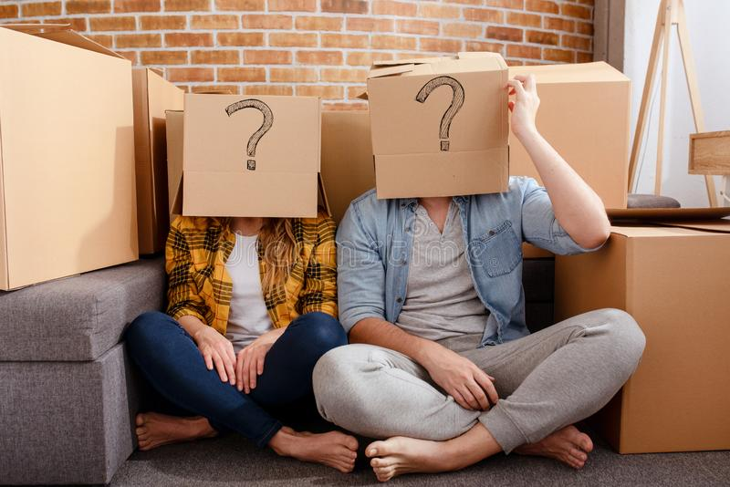Confused couple of having to move and arrange all the packages. Concept of success, delusion, change , future, confusion royalty free stock photography