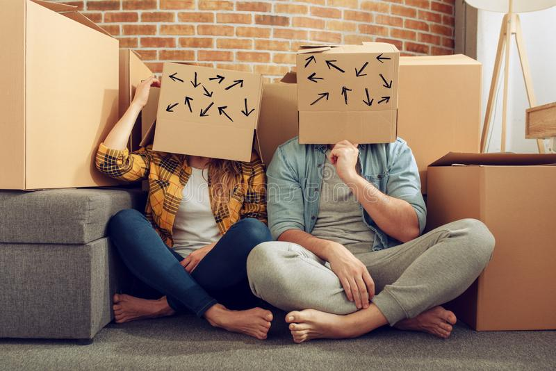 Confused couple of having to move and arrange all the packages. Concept of success, delusion, change , future, confusion stock photography