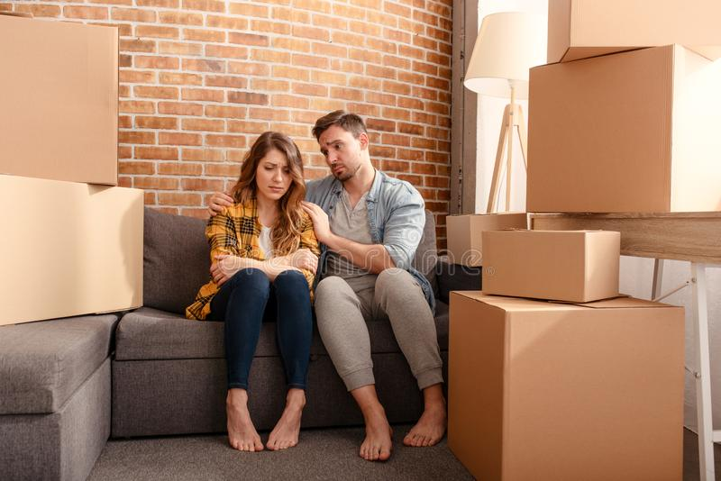 Confused couple of having to move and arrange all the packages. Concept of success, delusion, change and future royalty free stock images