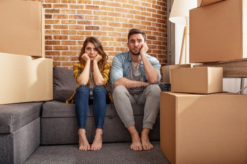 Confused couple of having to move and arrange all the packages. Concept of success, delusion, change and future royalty free stock photo