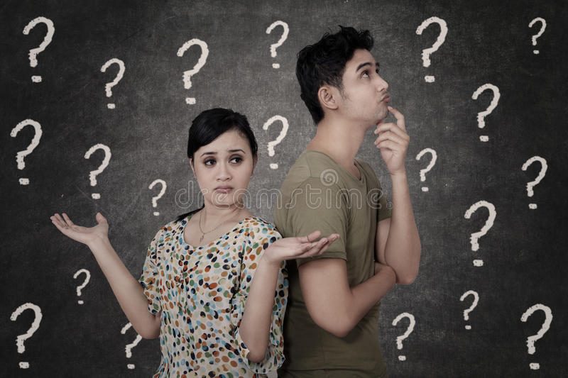 Confused couple with question marks on blackboard royalty free illustration