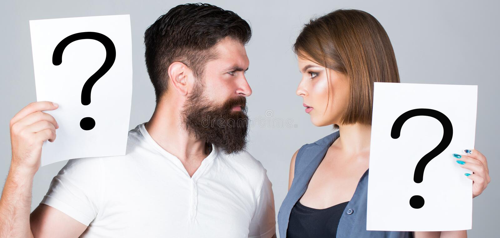 Confused couples with question marks. Conflict between two people. Pensive man and a thoughtful woman, conflict royalty free stock photography