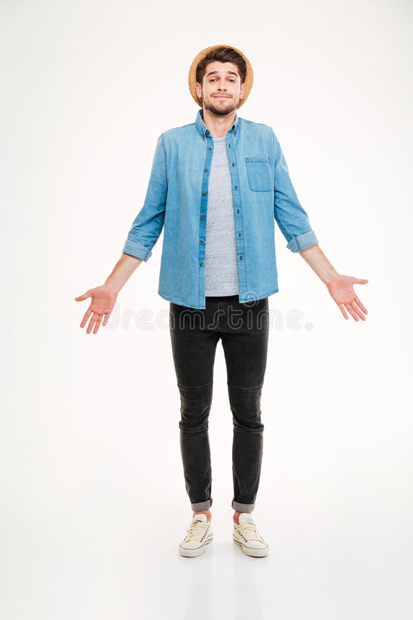Confused cute young man in jeans shirt standing and shrugging. Over white background royalty free stock images