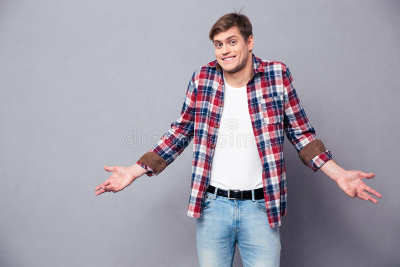 Confused cute young man standing and shrugging. Confused cute young man in plaid shirt and jeans standing and shrugging over grey background royalty free stock photography