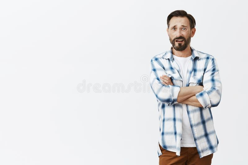 Confused dad watching news being shocked with nonsense reporter tells, disagree with strange opinion. Portrait of stock photos