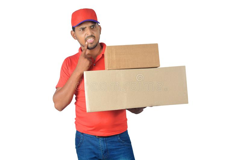 Confused delivery man holding carton box in uniform stock image