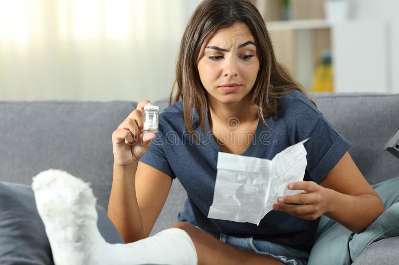 Confused disabled girl reading a leaflet of painkiller pills royalty free stock images