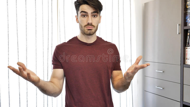 Confused or doubtful young man shrugging. While looking at camera, opening his arms. Indoors shot in a living room royalty free stock image