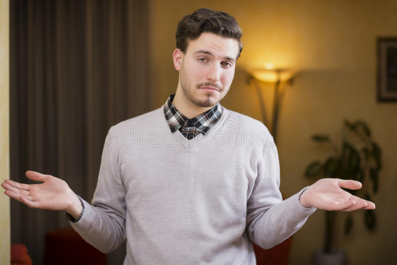 Confused or doubtful young man shrugging with palms open. Indoor shot in a house stock photo