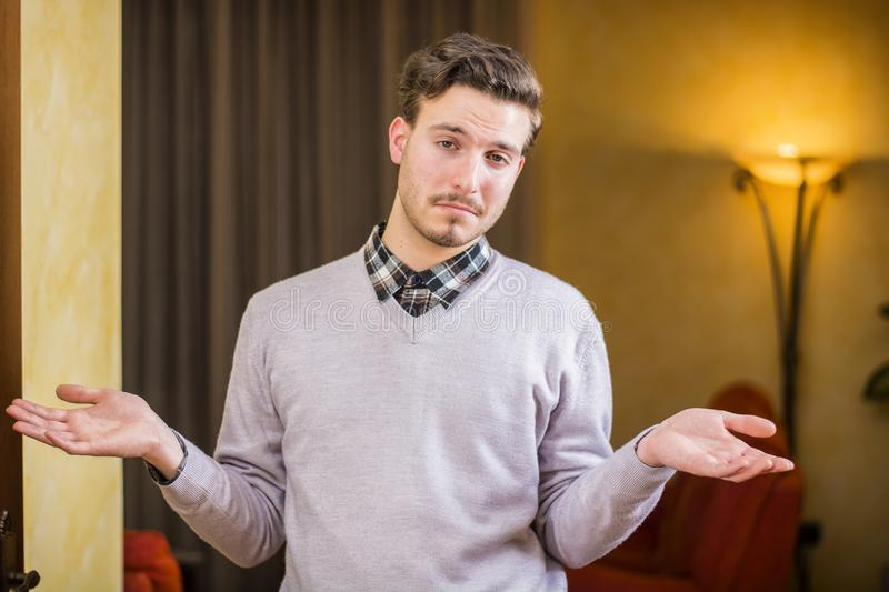 Confused or doubtful young man shrugging with palms open. Indoor shot in a house stock image