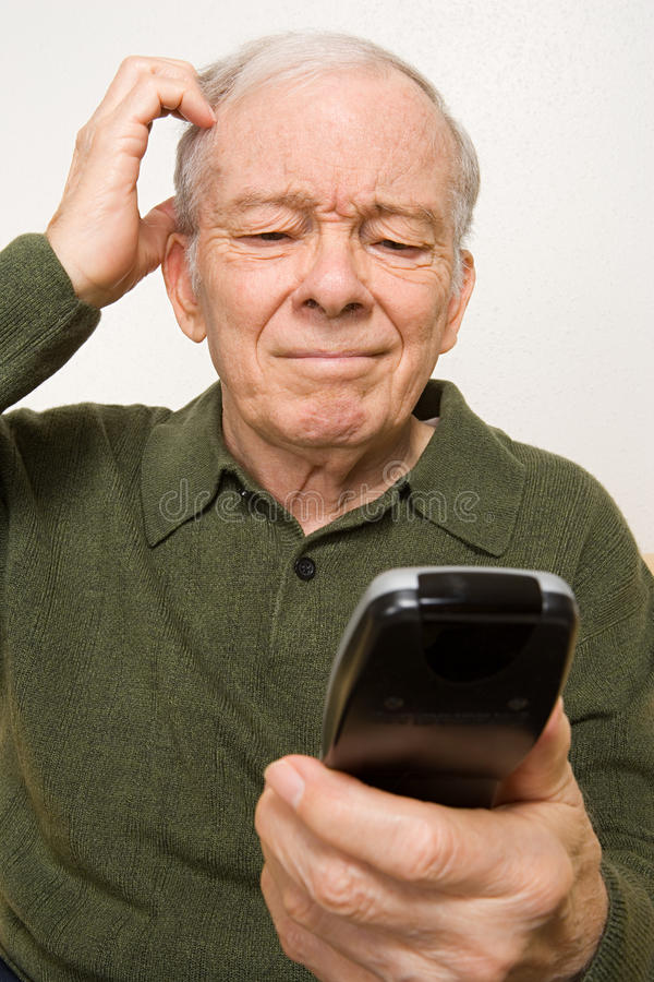 Confused elderly man with remote control. Confused elderly men with remote control royalty free stock photo