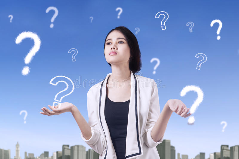 Confused female worker and question mark. Picture of a confused female worker thinking idea with question marks on the sky royalty free stock photos