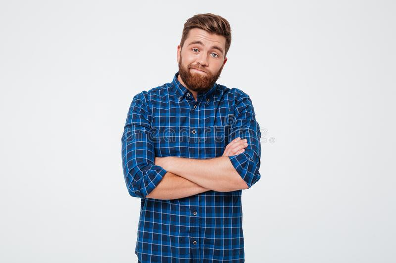 Confused frustrated bearded man standing with arms folded royalty free stock photo