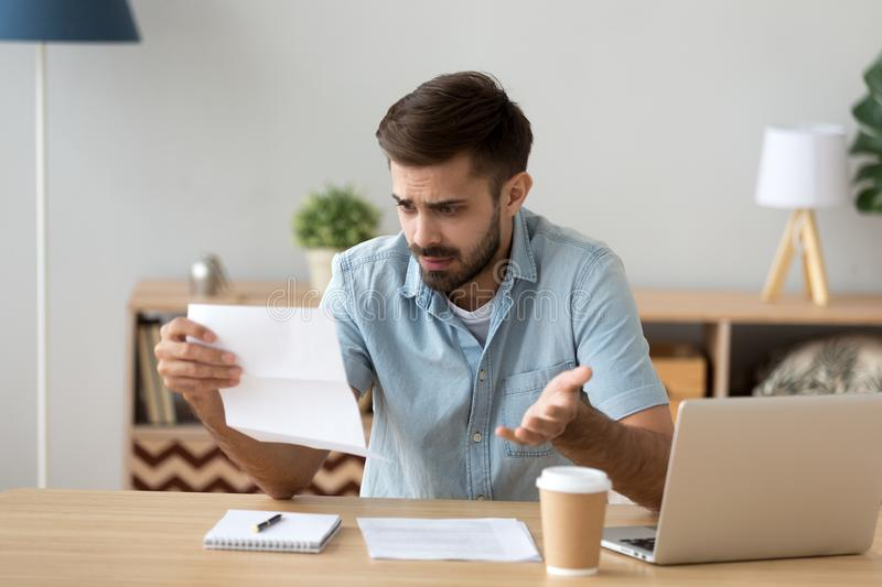 Confused frustrated man holding mail letter reading shocking unexpected news stock image