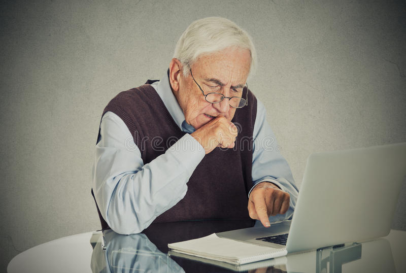 Confused grandfather using a pc. Computer sitting at desk stock photo