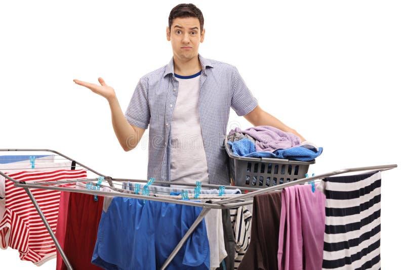 Confused guy holding laundry basket behind clothing rack dryer royalty free stock image