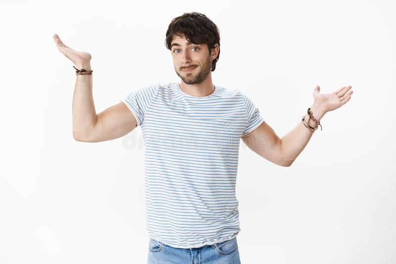 Confused guy not knowing answer, being clueless raising hands sideways with shoulder shrug and apology smirk standing. Unaware, being questioned and uncertain stock photos