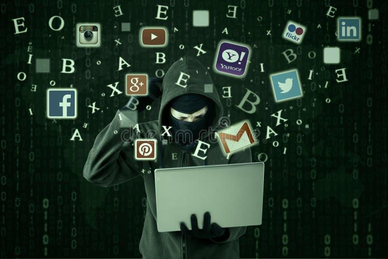 Confused hacker stealing social network id. JAKARTA, SEPTEMBER 21, 2015: Image of male hacker wearing mask and looks confused while stealing social media id like royalty free stock image