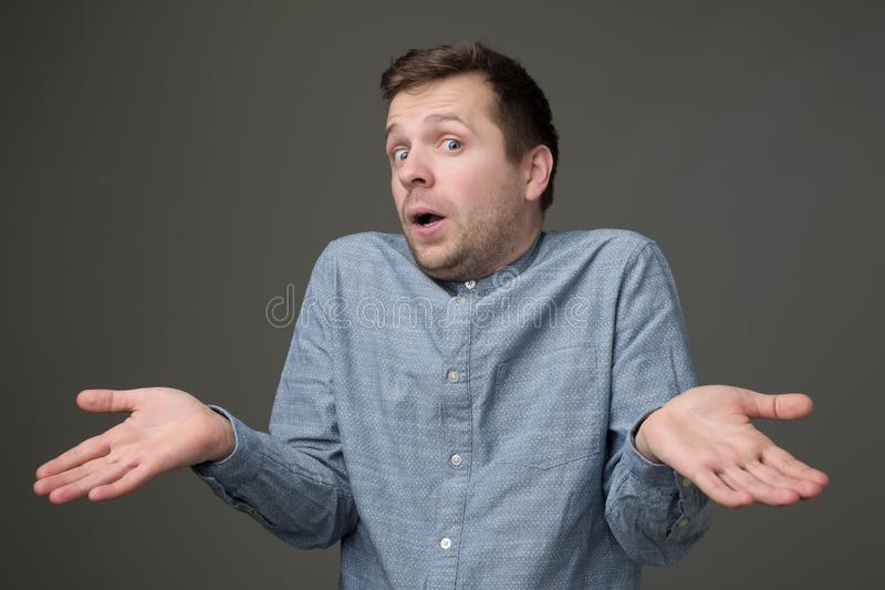 Guy showing I have no idea gesture, shrugging shoulders and raising hands. Confused handsome guy showing I have no idea gesture, shrugging shoulders and raising royalty free stock photography