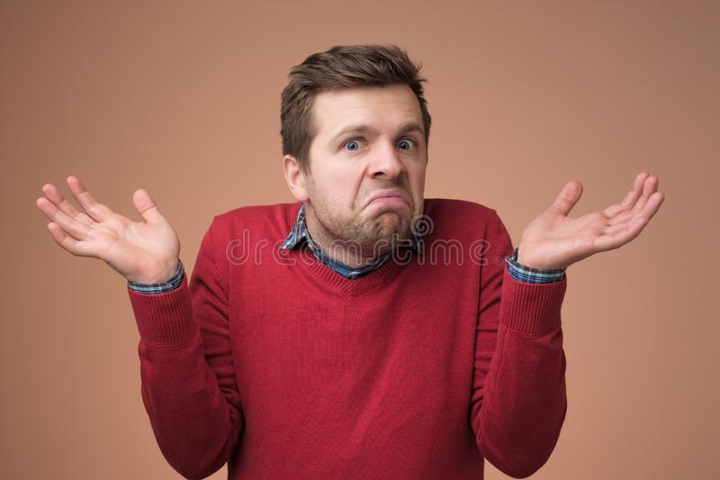 Guy showing I have no idea gesture, shrugging shoulders and raising hands. Confused handsome guy showing I have no idea gesture, shrugging shoulders and raising royalty free stock images