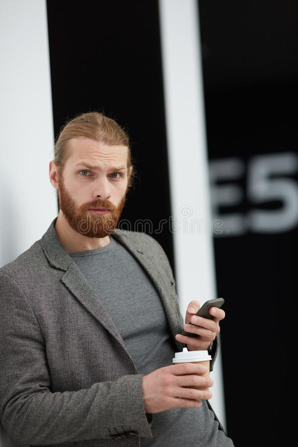 Confused handsome man with phone. Portrait of serious confused handsome young man with beard using smartphone and drinking coffee royalty free stock photography