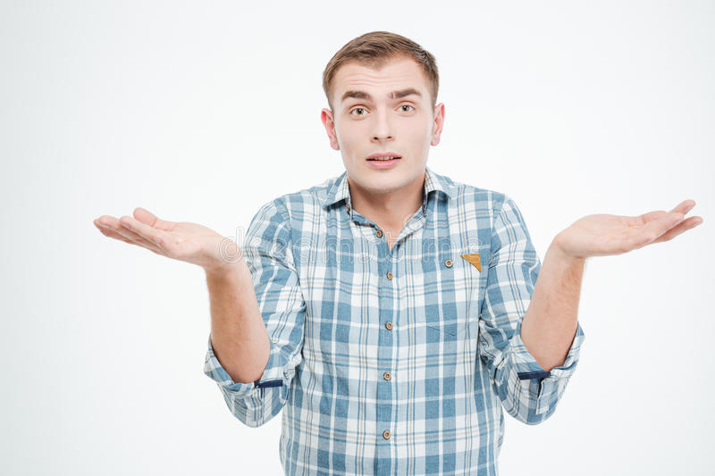Confused handsome young man holding copuspace on both palms. Over white background stock photos
