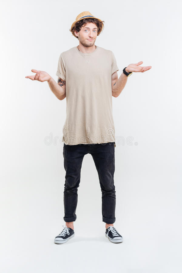 Confused handsome young man standing and shrugging. Over white background royalty free stock photo