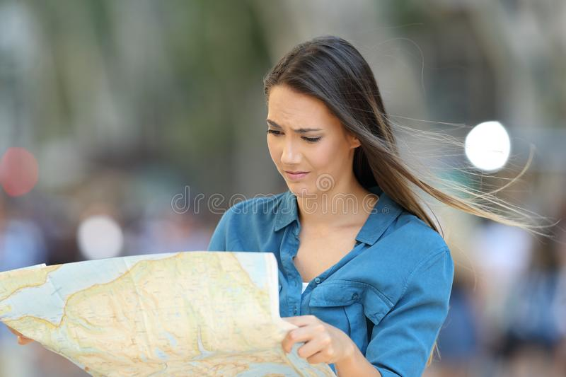 Confused lost tourist reading a map searching location. On a city street royalty free stock photography