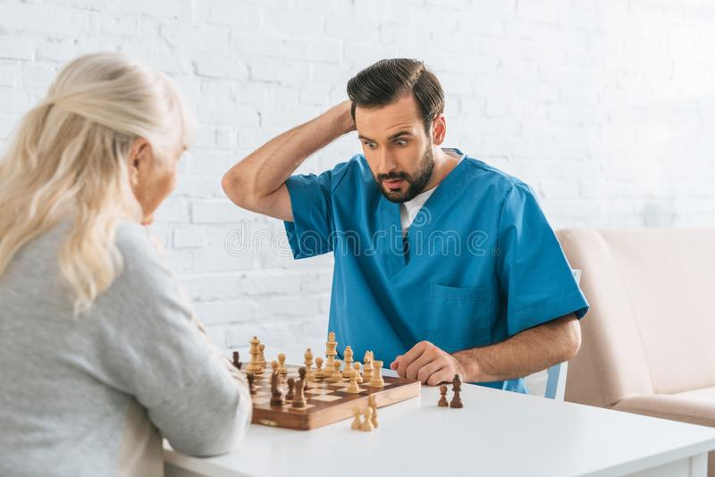 Confused male caregiver playing chess. With senior woman royalty free stock image