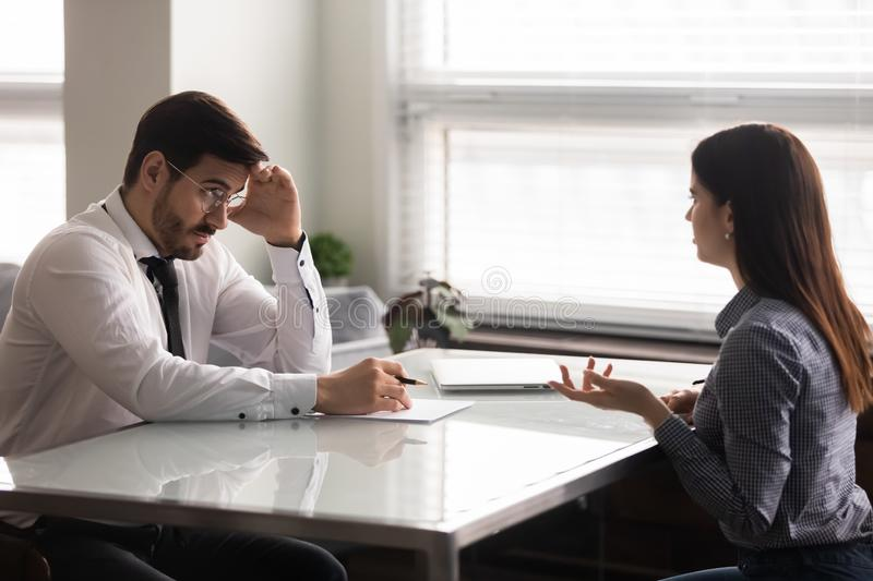 Confused male hr manager listening to female job applicant. stock image