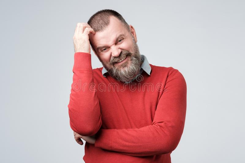Confused man with beard scratching head looking at camera stock images