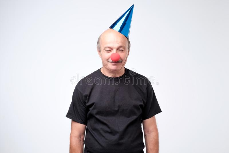 Confused man on clown hat looks with hesitant expression. Isolated over white background royalty free stock photography